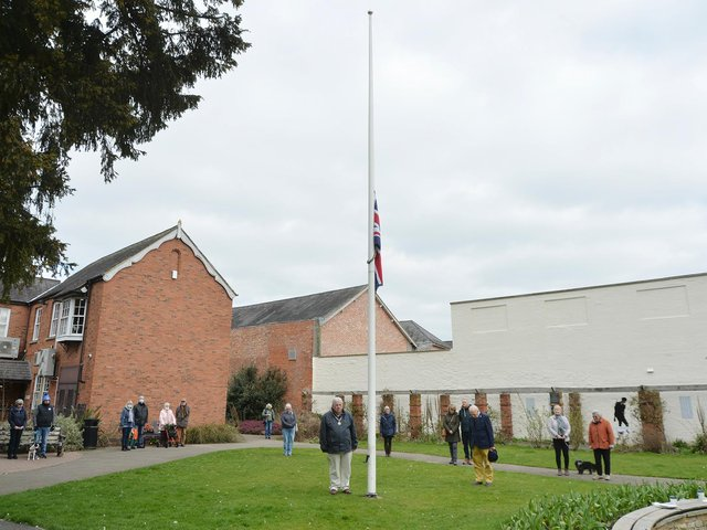 People stand for a minute silence at the memorial gardens at noon to remember those who died of Covid over the past year. PICTURE: ANDREW CARPENTER
