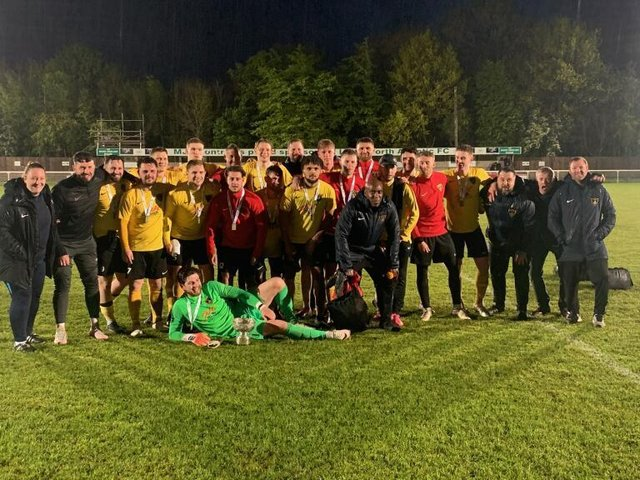 The Harborough Town players and staff celebrate after they beat ON Chenecks 2-0 in the final of the United Counties League's supplementary competition on Tuesday night. Picture courtesy of Harborough Town FC