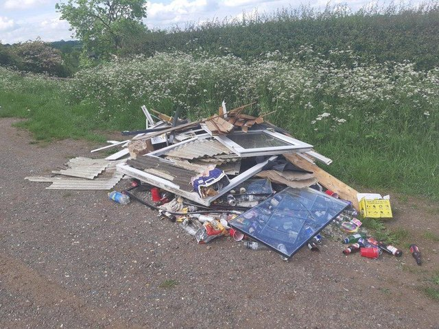 Fly-tippers have piled up a stack of building waste, including window frames, as well as beer bottles and other rubbish on Mowsley Road, Saddington, near Fleckney.